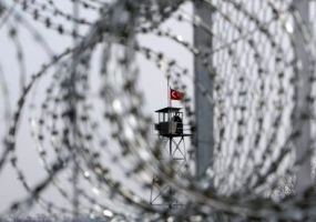 A Turkish military watchtower is seen through the barbed wire of a fence, which is being constructed, along the Greek-Turkish borderline near Orestiada town February 6, 2012. Greece is building a 12.5 km (8 miles) fence on its border with Turkey to prevent a wave of illegal immigrants from flowing into the country. Asian and African migrants increasingly use the northern Greece Evros border with Turkey to reach the EU, after the bloc stepped up surveillance at its sea borders and Spain and Italy signed repatriation deals with African countries.   REUTERS/Vassilis Ververidis/Motion Team             (GREECE - Tags: POLITICS BUSINESS SOCIETY IMMIGRATION CRIME LAW TPX IMAGES OF THE DAY)