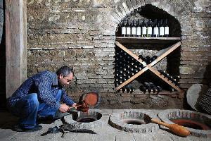 Gela Patalishvili, a wine engineer at the Pheasant's Tears wine cellar unseales and tries the wine from qvevri in Sighnaghi, Kakheti. Sept. 22, 2011.