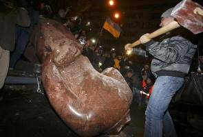 A man holds a sledgehammer as he smashes a statue of Soviet state founder Vladimir Lenin, which was toppled by protesters during a rally organized by supporters of EU integration in Kiev, December 8, 2013. Crowds toppled a statue of Soviet state founder Vladimir Lenin in the Ukrainian capital and attacked it with hammers on Sunday in the latest mass protests against President Viktor Yanukovich and his plans for closer ties with Russia. REUTERS/Stoyan Nenov (UKRAINE  - Tags: POLITICS CIVIL UNREST)