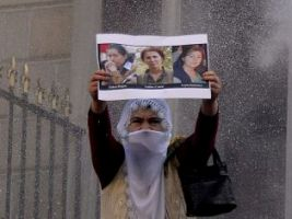 """A Kurdish woman holds a placard with pictures of the three Kurdish women killed in Paris during a demonstration on January 9, 2014 in Istanbul to mark the killing of the three top Kurdish activists Sakine Cansiz, Fidan Dogan and Leyla Soylemez, shot dead in the French capital one year ago.  Turkish police on Thursday fired tear gas and plastic bullets at hundreds of demonstrators marching to the French consulate demanding justice for three female Kurdish rebels killed a year ago in Paris. Between 500 to 600 Kurdish protesters had gathered in front of Istanbul's Galatasaray High School, shouting """"We want justice"""" for the three victims. The motives of the triple killing remain unclear. The three Kurdish activists including Sakine Cansiz -- a co-founder of the banned Kurdistan Workers' Party (PKK), were shot to death on January 9, 2013 at the Kurdish Information Centre in Paris. AFP PHOTO / BULENT KILIC"""